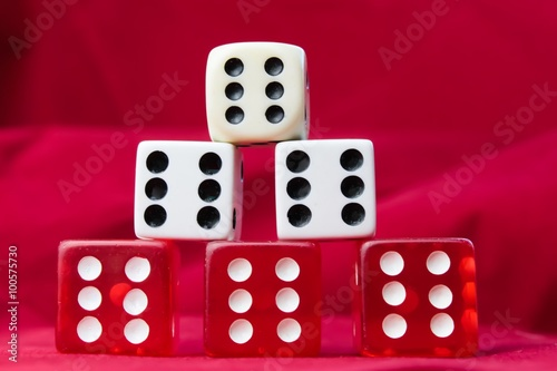A stack of die showing sixes against red felt плакат