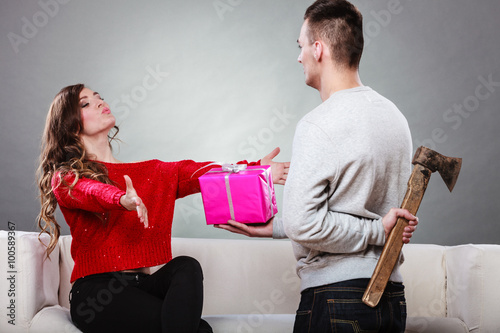 Fotografie, Obraz  Insincire man holding axe giving gift box to woman