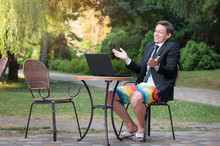 Businessman Dressed In Suit And Shorts Working With Laptop Outdo