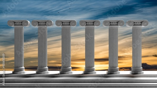 Photographie  Six ancient pillars with sunset sky background.