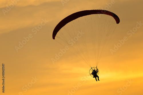 Foto auf AluDibond Luftsport Paramotor flying in the sunset sky, Silhouette shot.