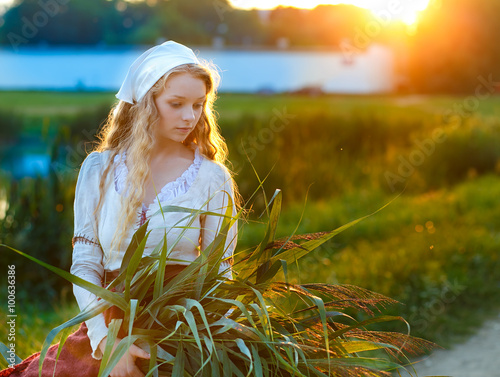 Fotografie, Obraz  Young peasant woman with corn leaves at sunset