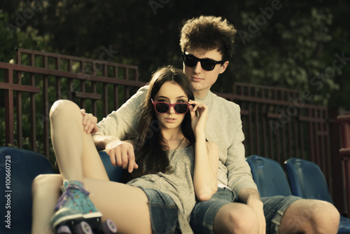 Poster Magasin de musique Portrait of a beautiful couple in sunglasses resting on the podium, lifestyle