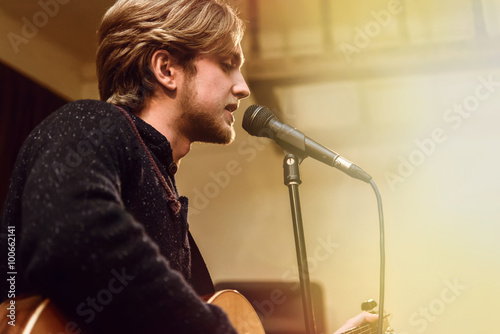 stylish vocalist with beard performing lyrical song on stage wit