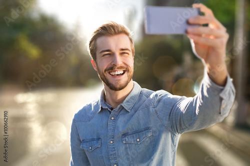 Fotografie, Obraz  Pohledný muž vezme selfie venku
