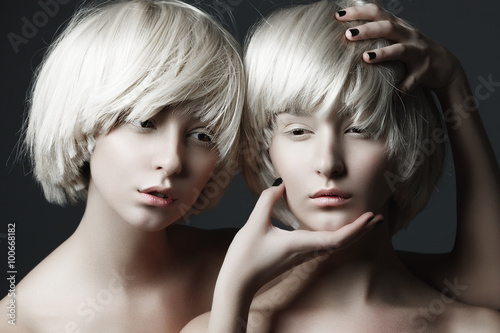 Obraz na plátně  Portrait of two beautiful girls twins with closed eyes in studio, closeup