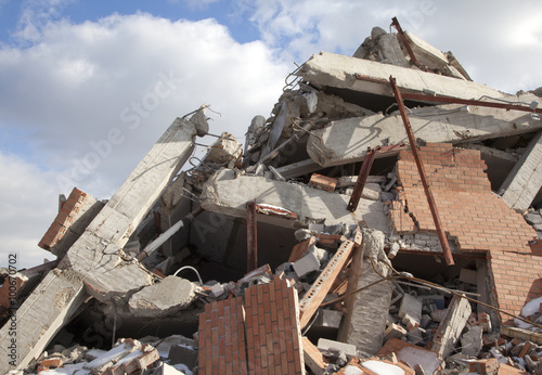 Fotografía  Rubble pile of wrecked building, blue sky and clouds, 2015.