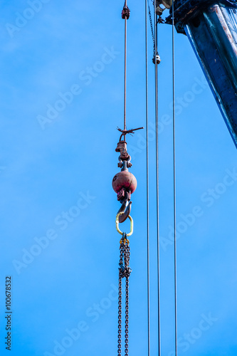 Keuken foto achterwand Schip Weight with hook and chain hanging from crane on blue sky