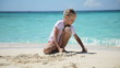 Young girl playing on a tropical beach with seashells, sand and corals.little girl playing with sand on tropical beach.Travel concept.Family,summer vacation.