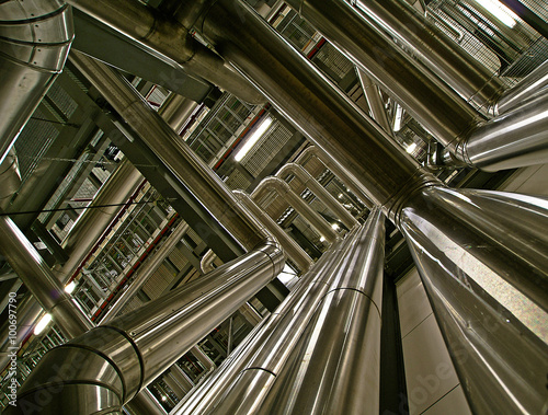 Tuinposter Industrial geb. ifferent size and shaped pipes and valves at a power plant