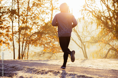 Foto  Young man running during autumn, winter morning