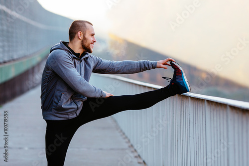 Fotografia, Obraz Athletic runner doing stretching exercise, preparing for morning