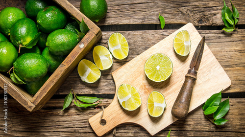 Sliced limes on a board with knife and box full .