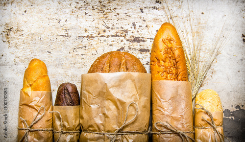 Keuken foto achterwand Brood Fresh bread wrapped in paper. On rustic background.