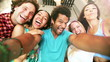 Five young adults laughing while taking a group selfie