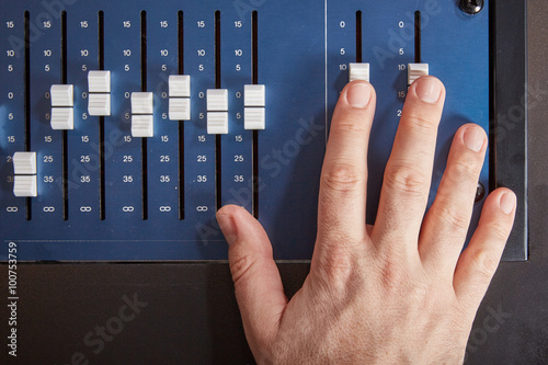 Fingers of audio engineer pushing the faders of an auio mixer Fototapeta