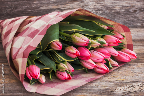 obraz lub plakat Bouquet of pink tulips wrapped in paper pack on wooden background