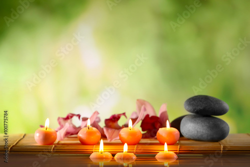Fototapety, obrazy: Spa still life with stones, candles and flowers in water on natural blurred background