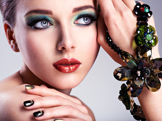 FototapetaBeautiful woman face with fashion green make-up and jewelry on h