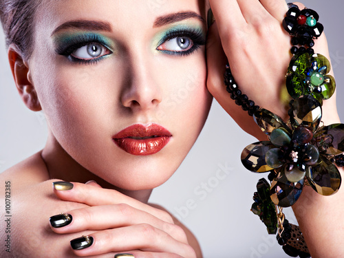 Beautiful woman face with fashion green make-up and jewelry on h - 100782385