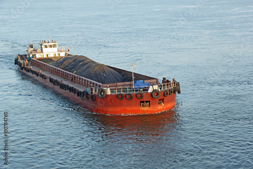 Fotografia  Iron ore mined in hinterland transported to the main harbor in large cargo boat