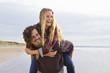 Laughing couple piggybacking on beach