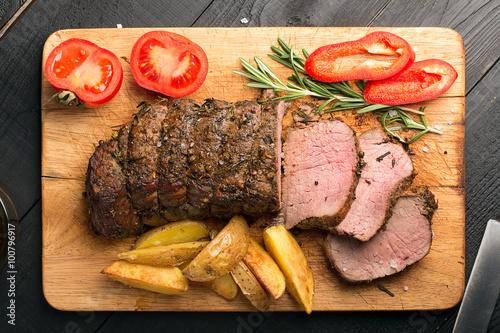 Obraz na plátne  Grilled beef on a cutting board