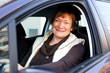 Happy mature woman sitting in new car