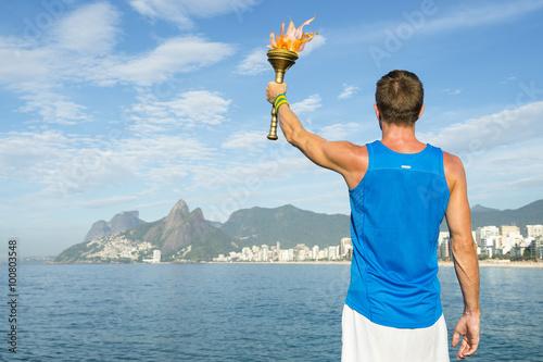 Fotografía  Athlete in athletic uniform standing with sport torch in front of Rio de Janeiro