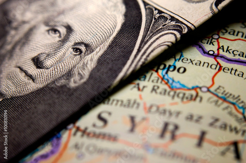 Fototapeta A dollar bill (figuring George Washington) on top of a map of Syria