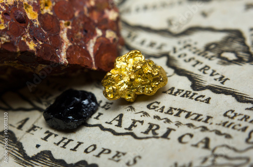 Photo  Close-up of ore deposits (gold, coal & bauxite) and an old map of Africa