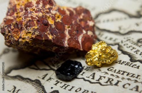 Fotografía  Primer plano de los depósitos de mineral (oro, carbón y bauxita) y un mapa antig