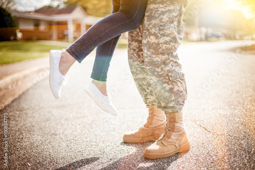 Obraz Young military couple kissing each other, homecoming concept, wa - fototapety do salonu