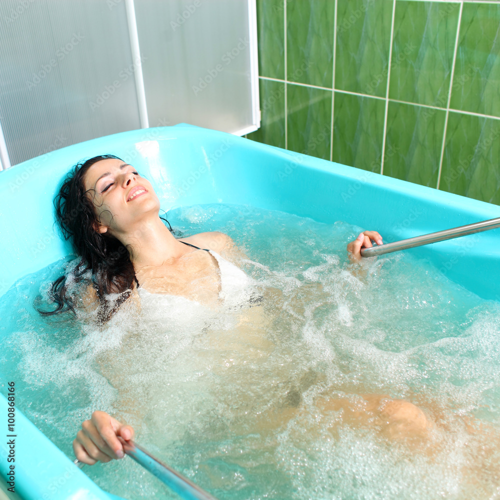 Fototapeta A girl and a hydromassage. She receives medical treatments for relaxation.
