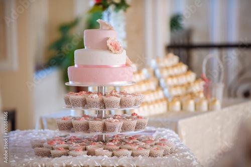 fototapeta na lodówkę big sweet multilevel white wedding cake with cream roses on a white table