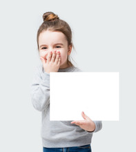 Giggles Happy Kid Girl Closes Face With Her Hand. Confused Little Girl Holding A Poster For Your Information. Gray Background