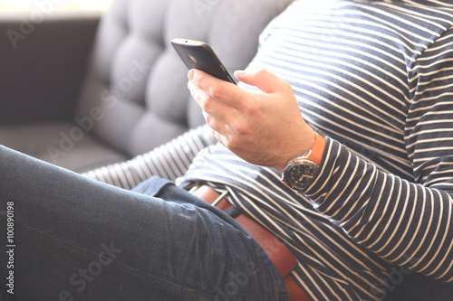 Young man sitting using a smart phone, Dressed casually  Vintage