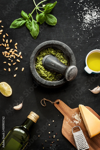 Fotografía  Green basil pesto - italian recipe ingredients on black chalkboard from above