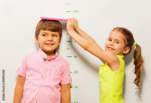 Fotografía  Boy and girl measure height by wall scale at home