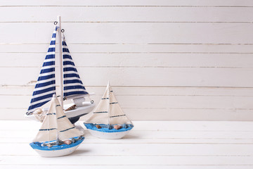NaklejkaDecorative sailing boats on wooden background.
