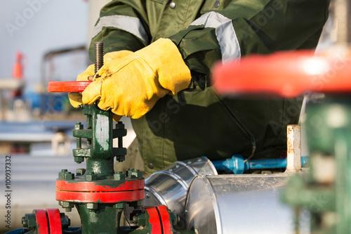 Photo  Oil worker turning valve