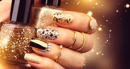 Fototapeta Do Spa Golden manicure with gems and sparkles. Bottle of nailpolish, trendy accessories