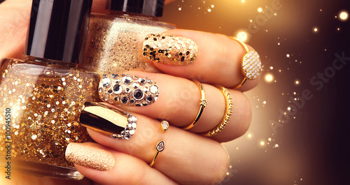 Golden manicure with gems and sparkles. Bottle of nailpolish, trendy accessories
