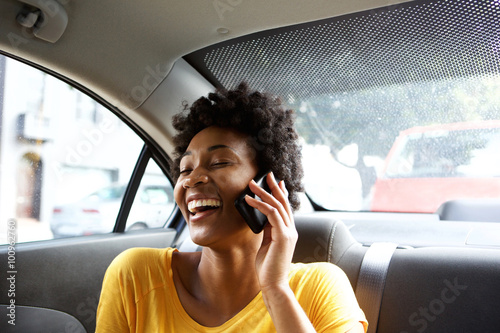 Laughing young woman in a car talking on mobile phone