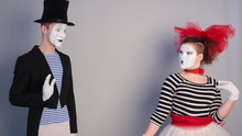 Male Mime Sharing Secret With Surprised Female Mime