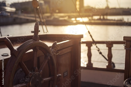 Tuinposter Schip Steering wheel of an old wooden sailing ship in a port at sunset