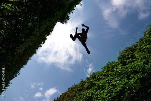 Fotografia  Man jumping over bushes