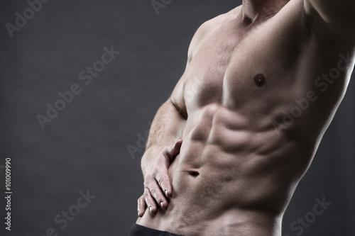 Fotografía  Handsome muscular bodybuilder posing on gray background