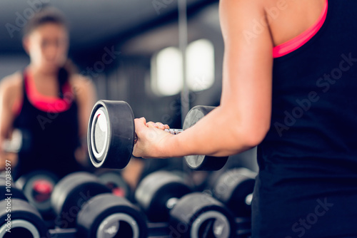 Foto op Plexiglas Fitness Woman exercising with dumbbell in health club