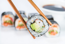 Close Up Of Chopsticks Taking Portion Of Sushi Roll On The Table